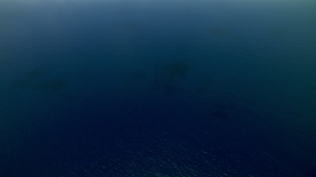 Aerial of blue Caribbean ocean with Montserrat Island in far distance.
