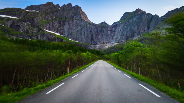 Aerial of country road with giant mountain cliff at the Lofoten Islands in Norway
