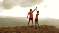 Aerial of couple running to mountain top and raising hands