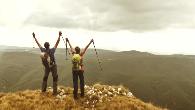 Aerial of hiking couple raising hands at mountain top