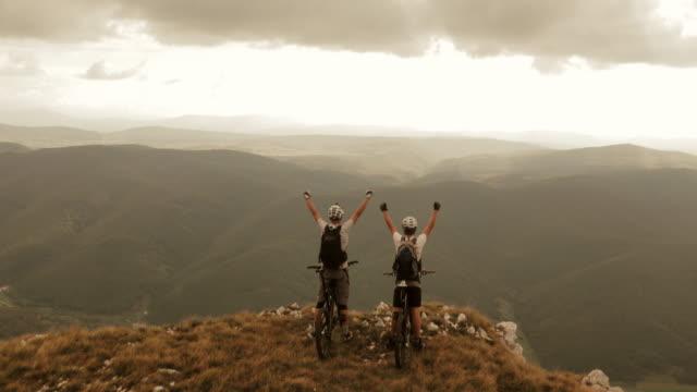 Luftaufnahme von Mountainbikern auf der ridge mit erhöhter Hände