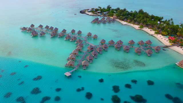 Aerial of picturesque overwater bungalows on a beautiful tropical island, drone flying backwards  - Bora Bora, French Polynesia