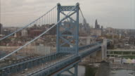 Aerial of the Ben Franklin Bridge in Philadelphia, continuing to the statue of Franklin on top of city hall.