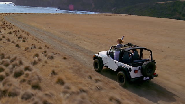 Aerial over 2 women in jeep / Flinders, Mornington Peninsula, Australia
