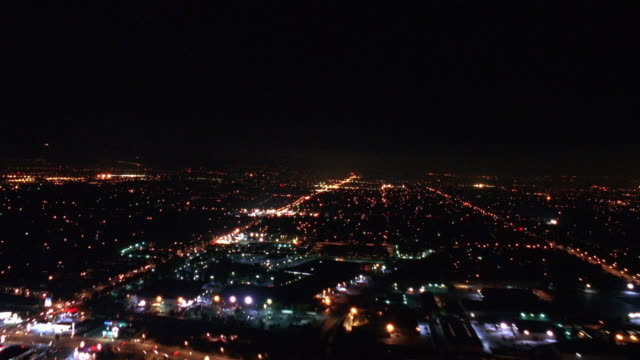 Aerial over airport runway and streets with traffic at night + landing point of view at night / Los Angeles