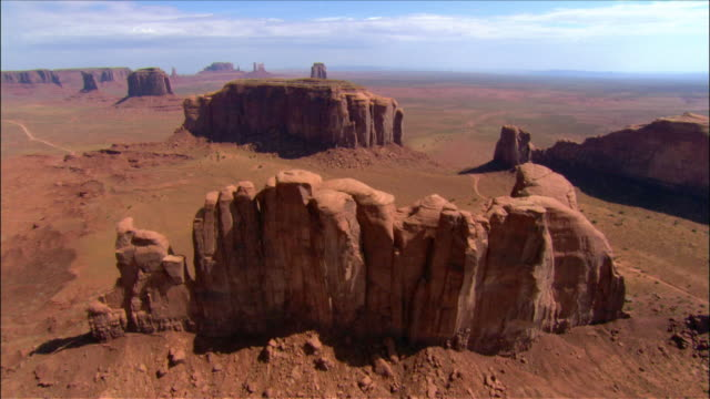 Aerial over 'Camel Butte' and 'Elephant Butte' rock formations / Monument Valley