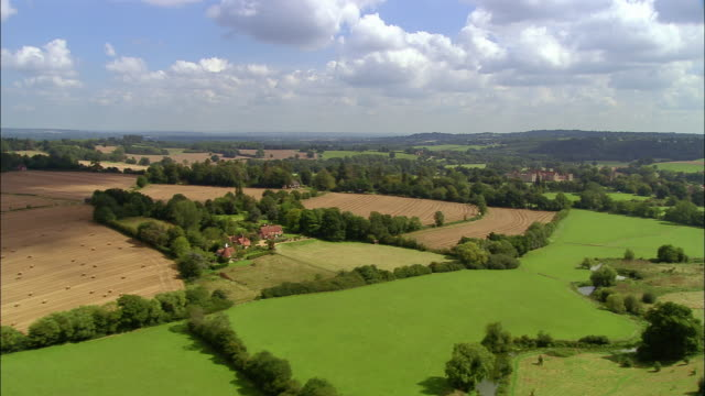 Aerial over cultivated fields in Weald of Kent to Penshurst village and Penshurst Place / England