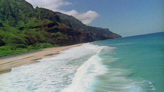 Aerial over ocean and beach around towards steep mountains / Hawaii