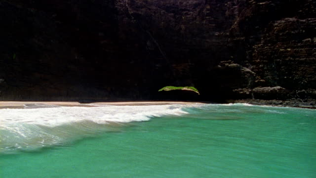 Aerial over ocean and beach passing through tunnel under mountain / Hawaii