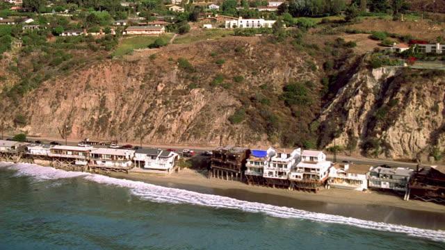 Aerial over Pacific Ocean and past beach in Malibu / California
