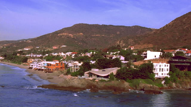 Aerial over Pacific Ocean and past beachfront residences in Malibu / California