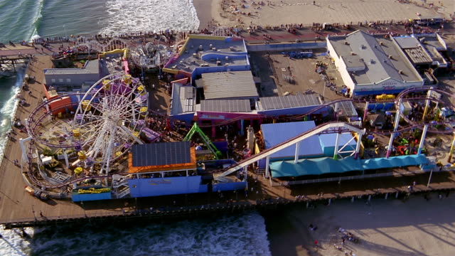 Aerial over people and rides on Santa Monica Pier / wide shot pier with city in background / Los Angeles