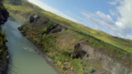 Aerial over river running through canyon between green hills / British Columbia, Canada