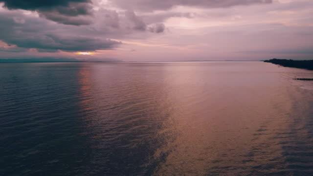 Flygfoto över sandy stränder längs kusten / solen reflekteras från ytan av havet