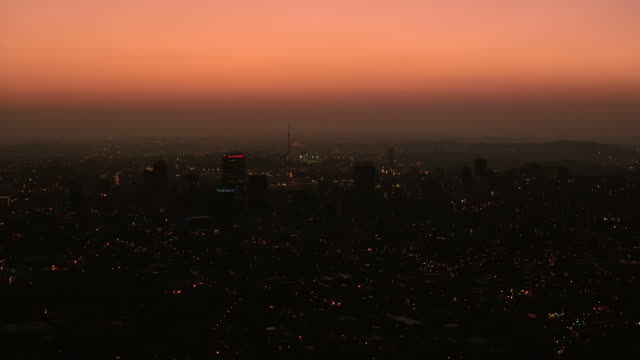Aerial over the Johannesburg CBD cityscape, at dusk