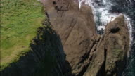 Aerial over top of cliff to view of Fingal's Cave on coast of Staffa Island / Scotland