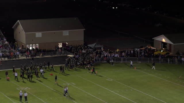 Aerial pan of high school football game as players go to locker room