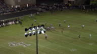 Aerial pan of high school football game at night