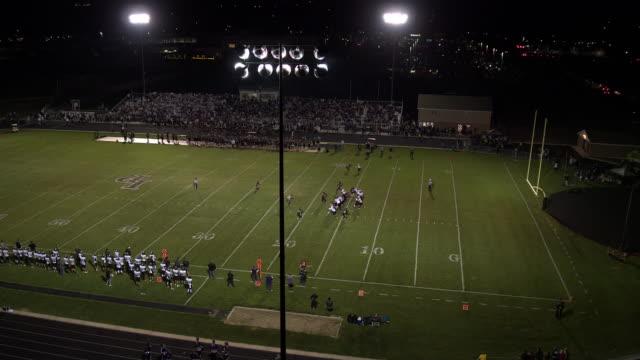 Aerial pan of high school football game at night