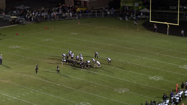 Aerial pan of high school football game during field goal attempt