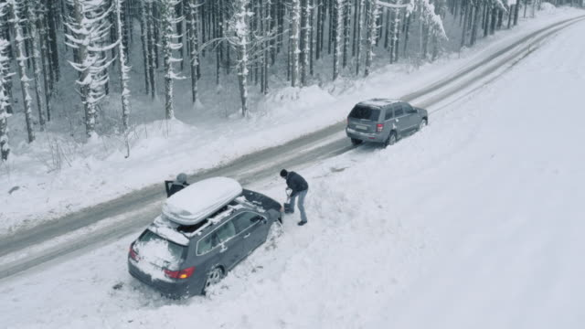 Aerial Passing driver helping a man dig his car out of snow