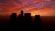 Aerial past downtown Los Angeles at sunset / California
