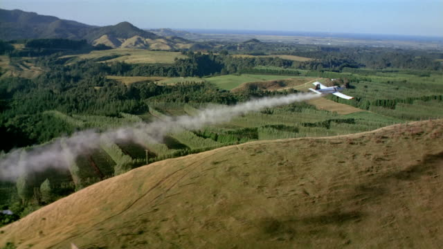 Aerial plane flying over agricultural plots and trailing smoke or spraying pesticide / New Zealand