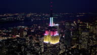 Aerial point of view around Empire State Building with other buildings below and in background at night / New York City