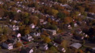Aerial point of view over houses and streets in suburban town in Autumn / Maine