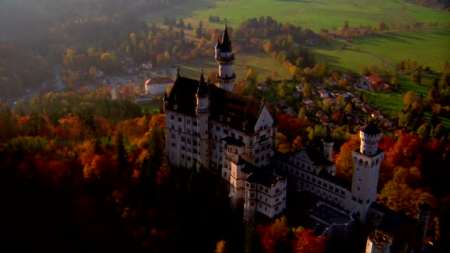 Aerial point of view over Neuschwanstein Castle on hilltop in Autumn / Bavaria, Germany