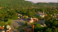Aerial point of view over small town in hilly tree-covered landscape / Greenville, South Carolina