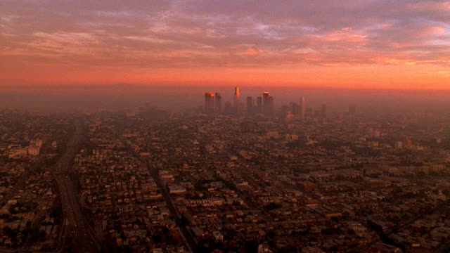Aerial point of view over smoggy Los Angeles towards downtown at dusk / California
