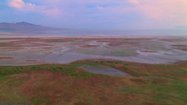 Aerial point of view over wetlands of Great Salt Lake with mountains in background / Utah