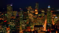 Aerial point of view past Space Needle then over downtown Seattle buildings at night / Washington