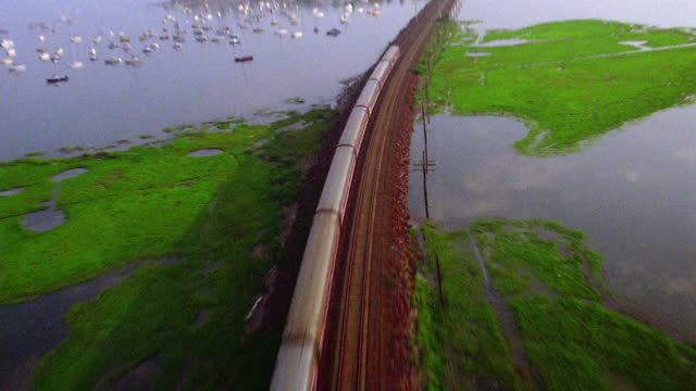 Aerial point of view past train on tracks surrounded by water and marshes / Hartford, Connecticut