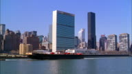 Aerial point of view United Nations building w/barge on East River in foreground