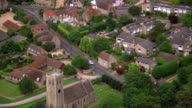 Aerial point of view zoom out from country church to village surrounded by green countryside / England
