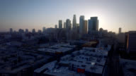 Aerial pull of downtown Los Angeles California backlit with the beautiful sunset