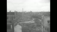 Aerial ruins of postWorld War II Tokyo / ground level of rubble / people clearing rubble / intact bank safe / VS ruins civilians in makeshift home...