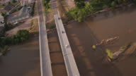 Aerial scene featuring a double highway crossing a shallow muddy river lined with trees and sandbars.
