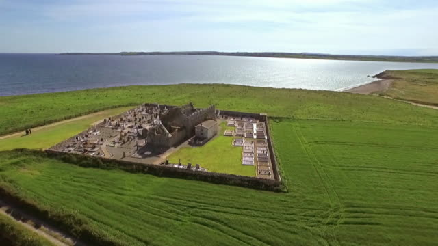 Aerial sequence showing views of the ruined Norman church of the Blessed Virgin Mary next to Bannow Bay in County Wexford, Republic of Ireland.