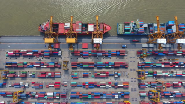 Aerial shot Container Cargo freight ship with working crane bridge in shipyard