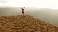 Aerial shot female runner on top of mountain raising hands
