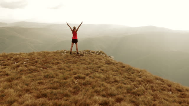 Aerial shot female runner on top of mountain raising hands