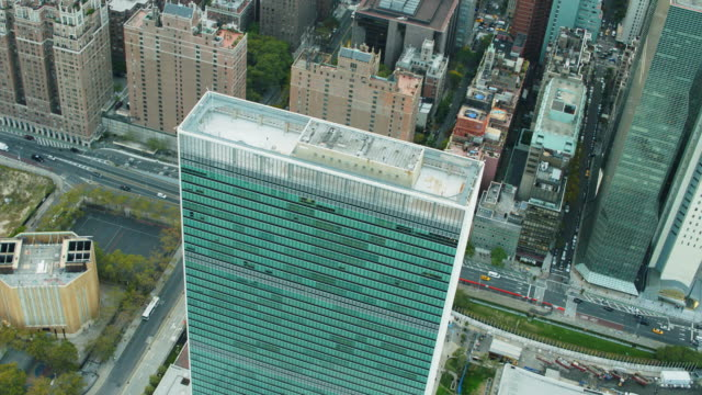 Aerial shot flying over UN building, FDR drive and East river in NYC