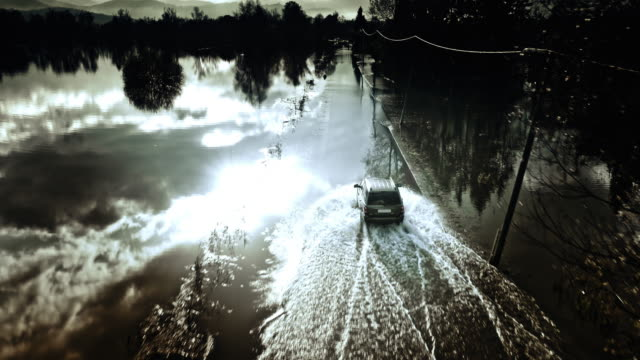 Aerial shot following a car driving on flooded road