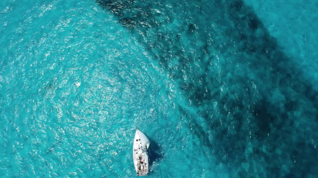 Aerial shot looking down at sailboat and beautiful clear blue ocean