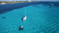 Aerial shot looking down flying past sailboat anchored in beautiful clear blue ocean