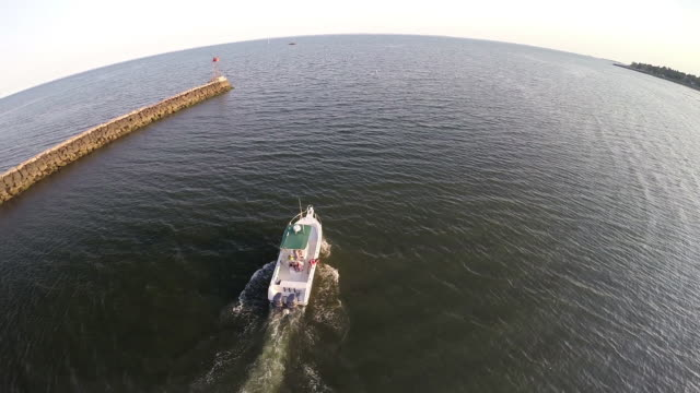 Aerial shot of a boat leaving a harbor