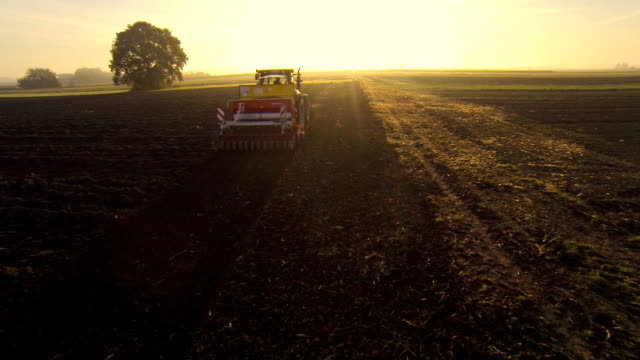 HD: Aerial Shot Of A Tractor Plowing The Field